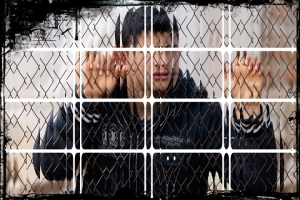 A Syrian refugee boy stands behind a fence